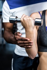 Cropped image of male trainer assisting fit woman