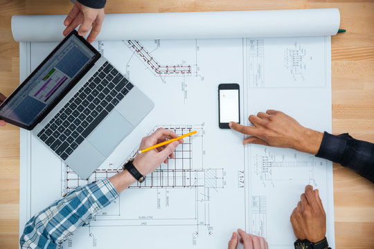 Group of people working with laptop, smartphone and blueprint
