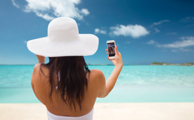 woman taking selfie with smartphone on beach