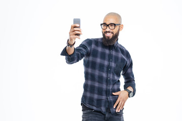 Cheerful african american man with beard smiling and taking selfie