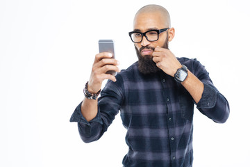 Baldheaded african american man touching moustache and taking selfie