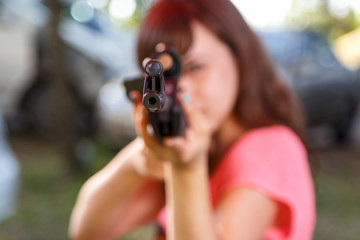 Young woman shooting from telescopic air gun, focus on front sig