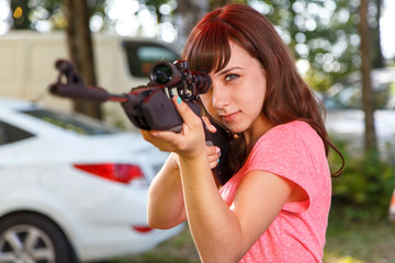 Cool female sniper aiming from telescopic rifle