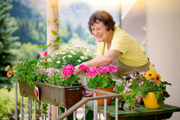 elderly woman with her flowers on balcony/gardening 10