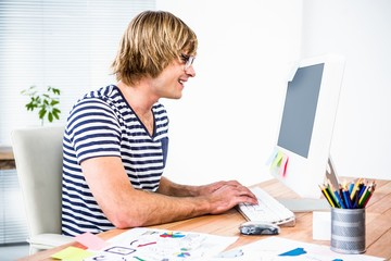 Smiling hipster businessman using his computer