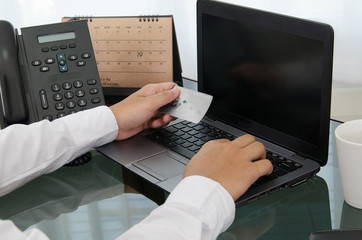 Hands holding a credit card and using laptop