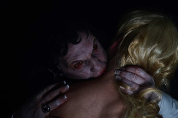 Portrait image of a male vampire biting his female victim.