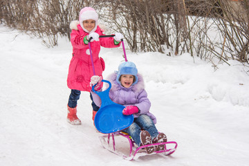 The older girl rolls the younger girl on a sled in the yard