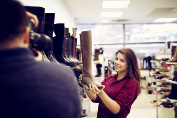 Woman is looking for a new pair of shoes while photographer is photographing her for stock market. Shallow depth of field.
