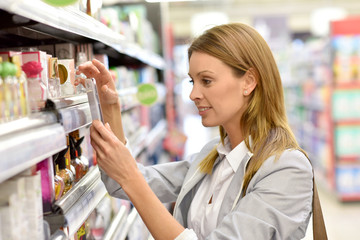 Woman customer scanning food products in grocery store