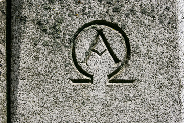 Alpha omega symbol carved in grey granite stone