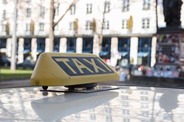 taxi sign on the roof of a car standing in street