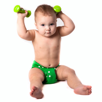 baby kid, toddler in green diapers  doing exercises with dumbbel