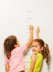Two kids read height at home wall