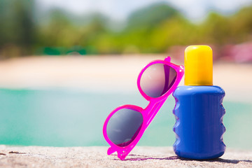 Sunscreen and sunglasses on sand at tropical beach