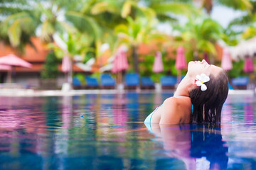 young woman with flower in hair taking spa in luxury pool