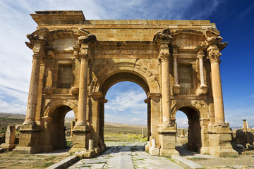 Photo on textile frame Algeria Algeria. Timgad (ancient Thamugadi). Paving stones of Decumanus Maximus street and 12 m high triumphal arch, called Trajan's Arch
