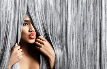woman look out throught grey hair and sending a kiss