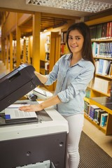 Smiling brunette student making a copy