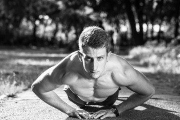 young muscular man push ups on walking road in a park