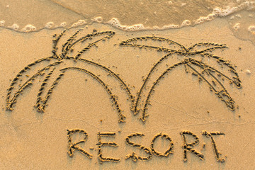 Resort word and palm tree - drawn on the sand beach with the soft wave.