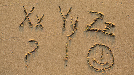 Letters of the alphabet written on sandy beach (from X to Z)