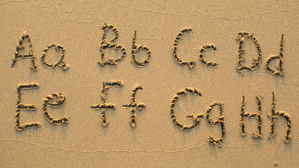 Letters of the alphabet written on sandy beach (from A to H)