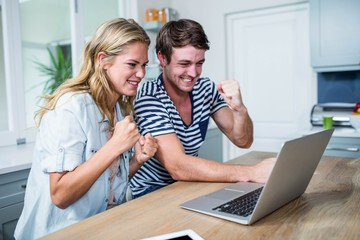 Happy couple watching videos on laptop