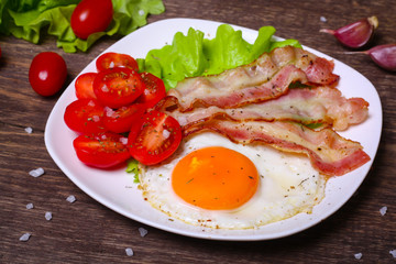Hearty breakfast. Fried egg with bacon and tomatoes on a wooden background