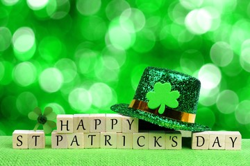 Happy St Patricks Day wooden blocks with leprechaun hat and shamrock over twinkling green background Wall mural