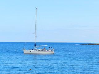 Парусная лодка в море на фоне горизонта