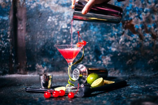 barman preparing and pouring red cocktail in marini class. cosmopolitan cocktail on metal background