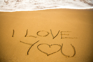 I Love You message written in sand; summer background, sea and sand background