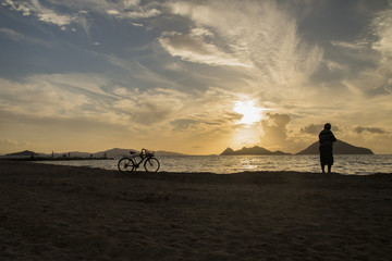 Man with bicycle watching sunset at the beach
