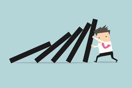 Businessman pushing hard against falling deck of domino tiles.