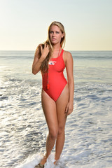 Stunning young Caucasian female lifeguard on the beach at sunrise - in red one piece swimsuit