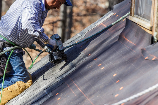 Roofer uses nail gun to secure shingles.