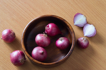 Shallots in wood bowl and wooden surface background, warm color tone
