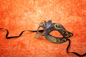 Mardi Gras mask on orange background.