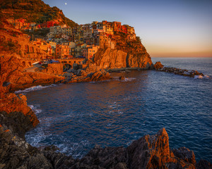 Warm sunset light over Manarola, one of the five villages forming Cinque Terre, the UNESCO heritage sites