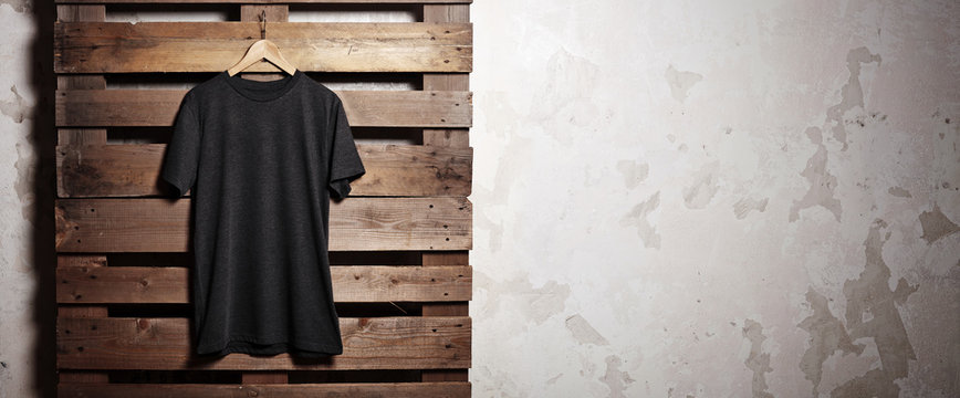Photo black tshirt  hanging in front of wood background. Wide