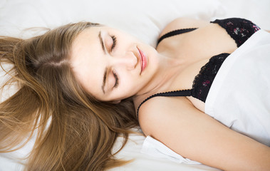woman lying in bed under sheet with closed eyes