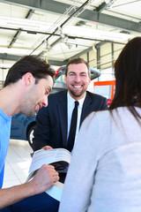 freundlicher Verkäufer mit Kunden beim Vertragsabschluss im Autohaus // friendly seller with customers at contract conclusion at the dealership