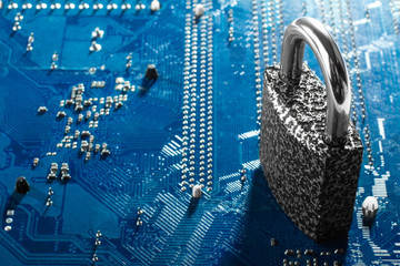 new padlock of iron lies on the back side of the motherboard. The concept of cyber security and cyber crime