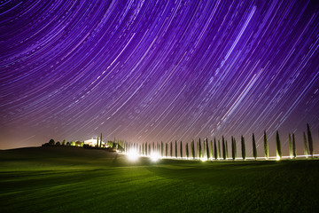 Beautiful Tuscany night landscape with star trails on the sky, cypresses and shining road in green meadow. Natural outdoor amazing fantasy background.
