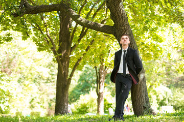 Man dressed suit stands nearthe tree