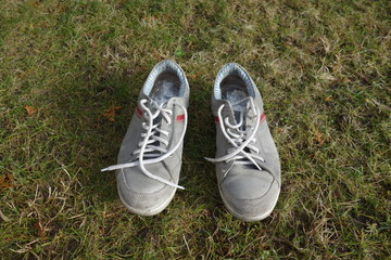 old dirty trainers on a grass