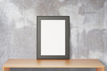 Blank black picture frame on wooden table and concrete wall, moc