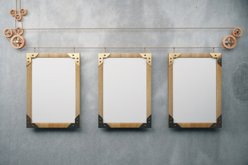 Blank wooden steampunk picture frames on grey concrete wall, moc