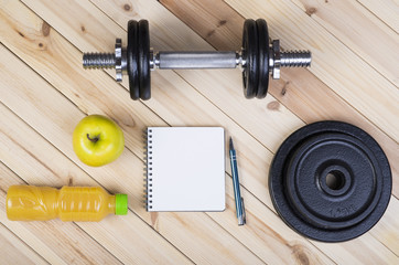 Sport Equipment. Dumbbells, Free Weights, Barbell, Apple, Orange Juice  And Notepad To Workout Plan On Boards. Sport Fitness Background